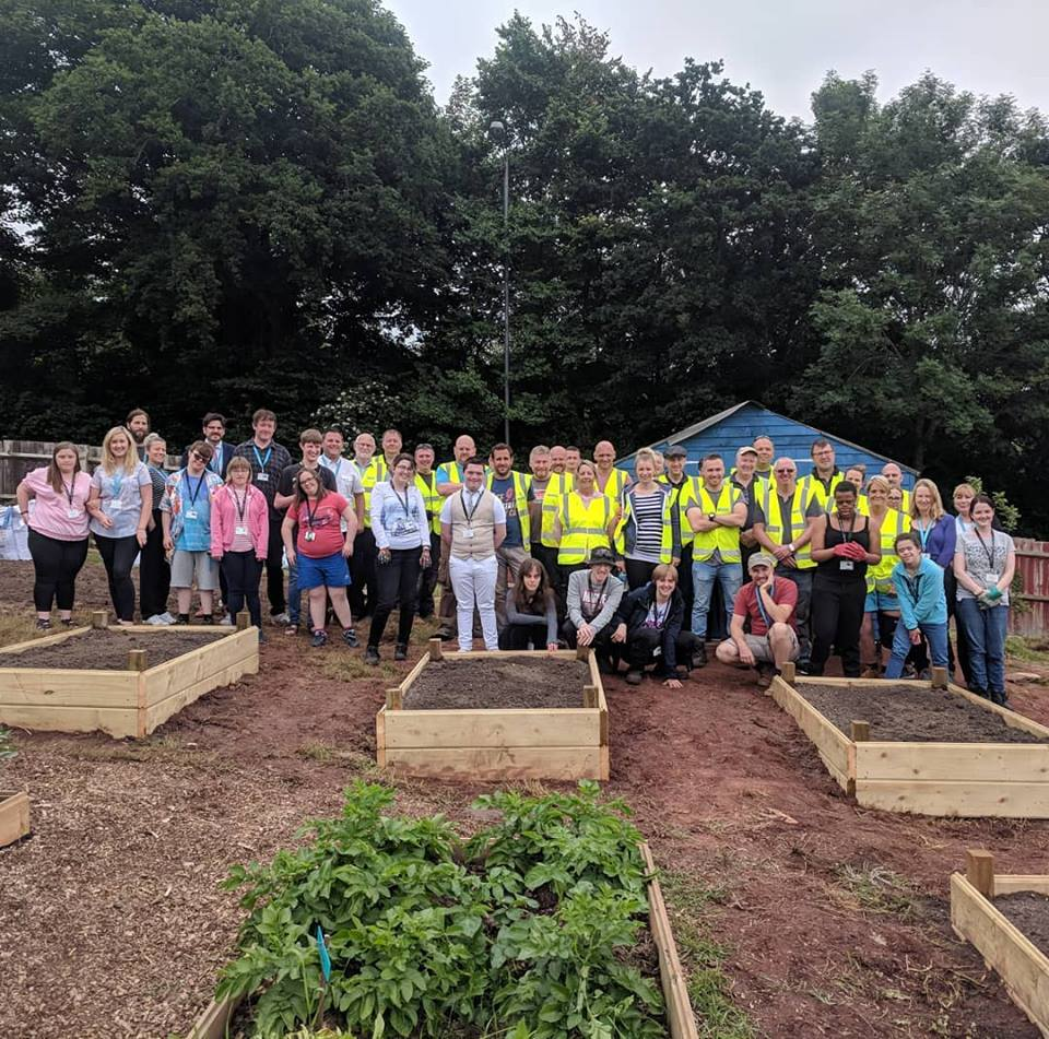 Volunteers stand in an allotment to pose for a photo