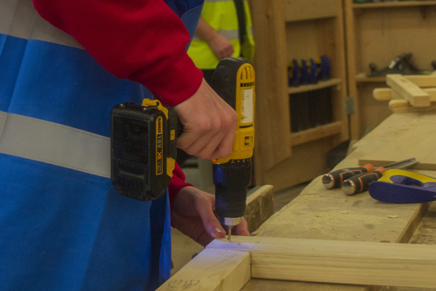 Carpentry. Bench joinery students drilling a frame