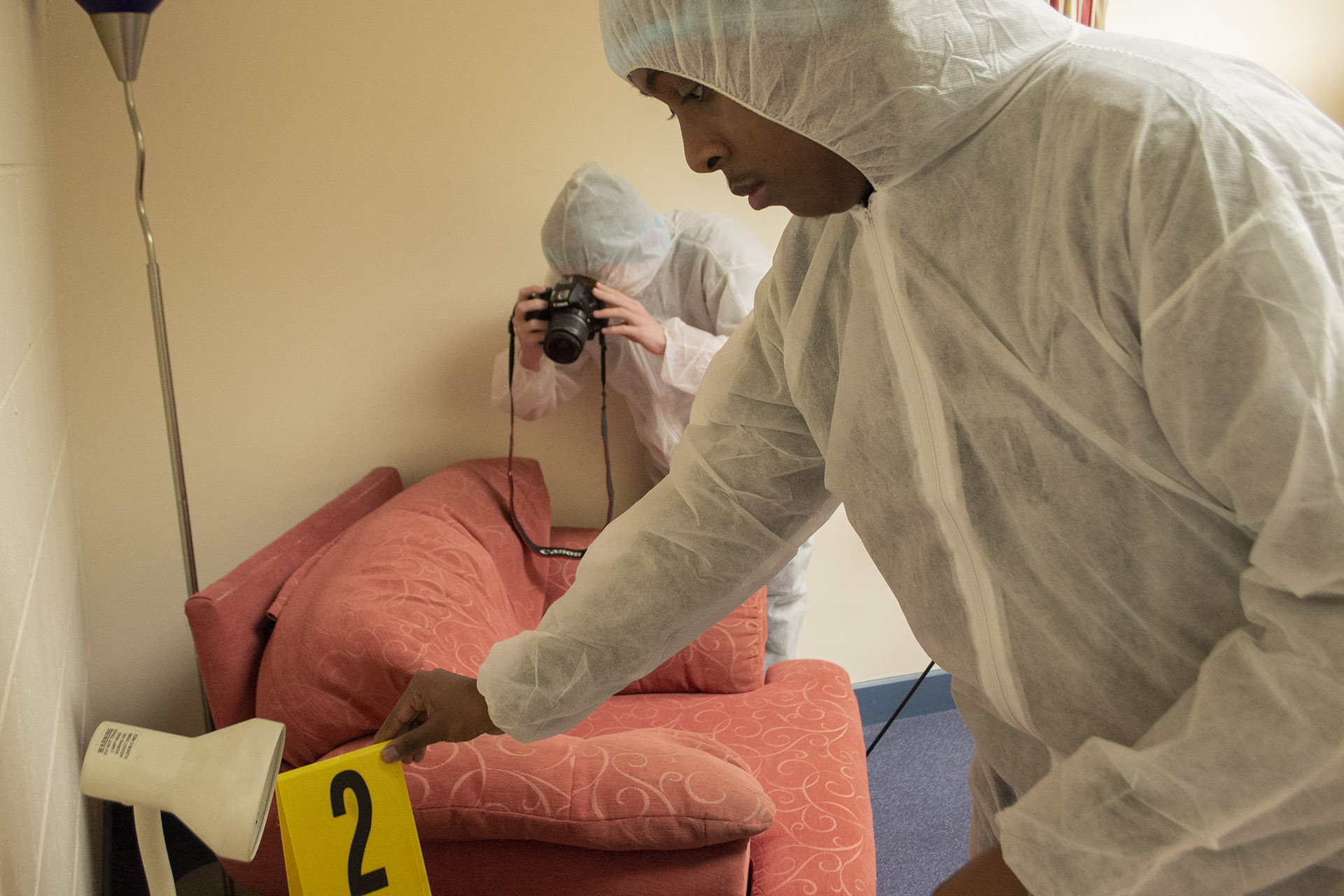 Forensics. Students in protective clothing reviewing crime scene