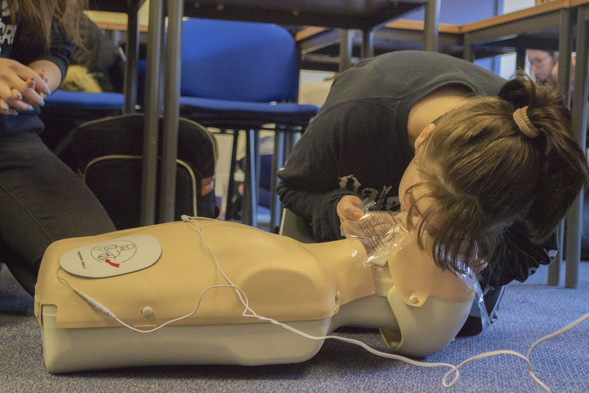 Student performing CPR on dummy