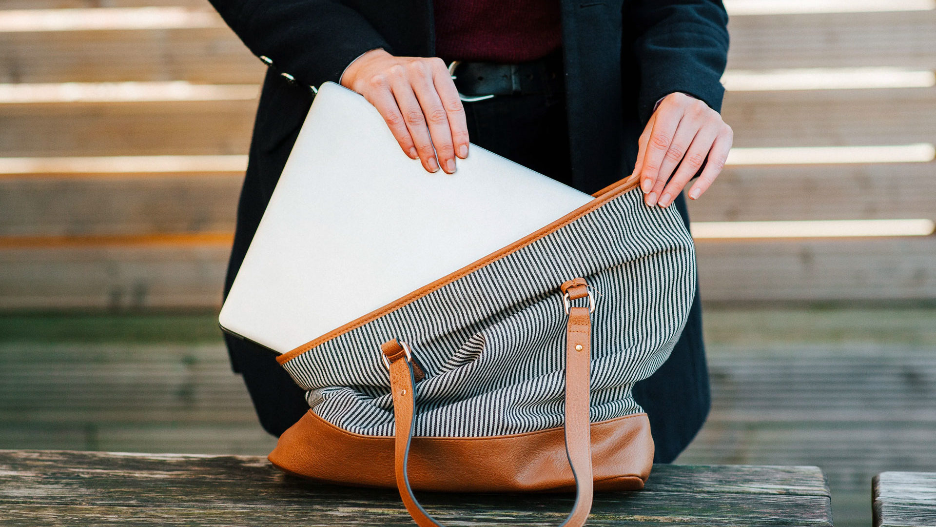Student putting laptop in bag