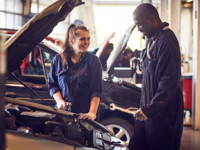 Two people working on car