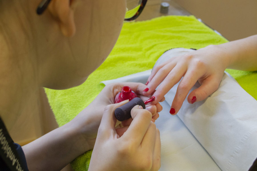 City of Bristol College nail student painting someone's nails red