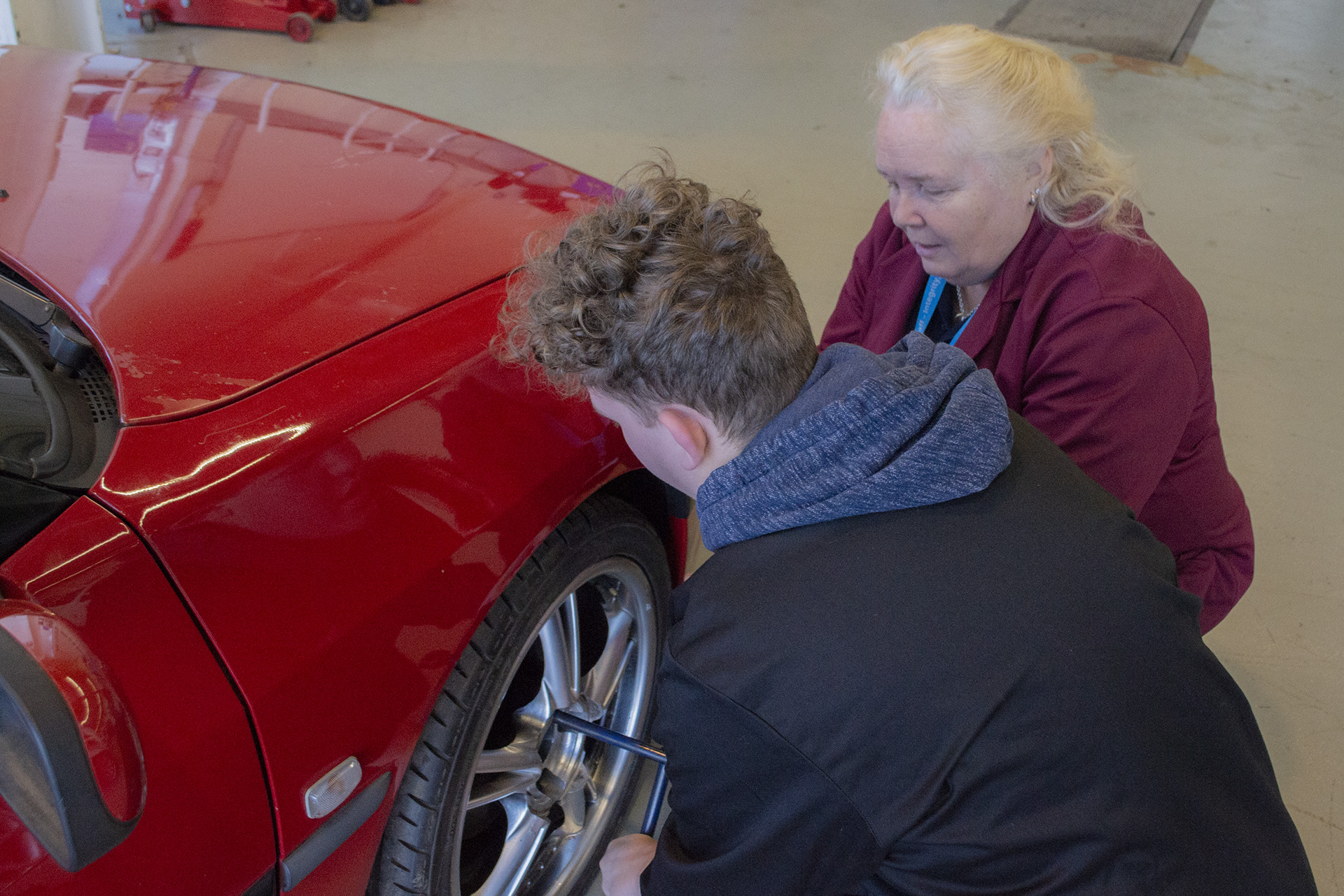 Tutor and student working on car