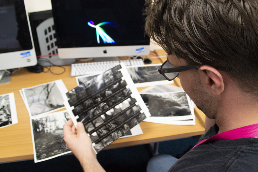 City of Bristol College photography student looking at pictures from a darkroom