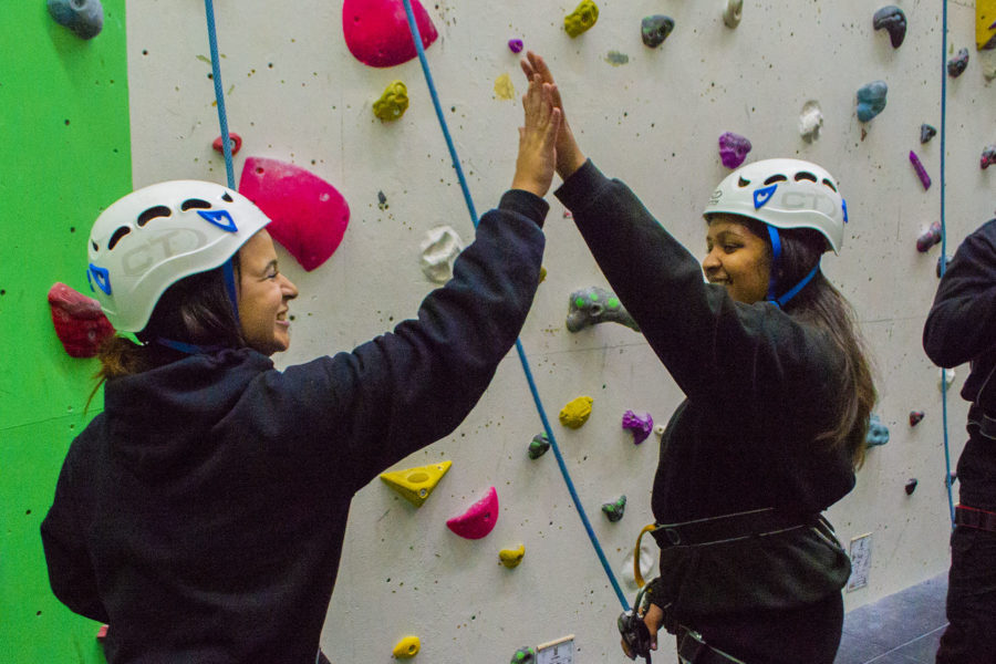 Public Services. Students at climbing wall, giving high five