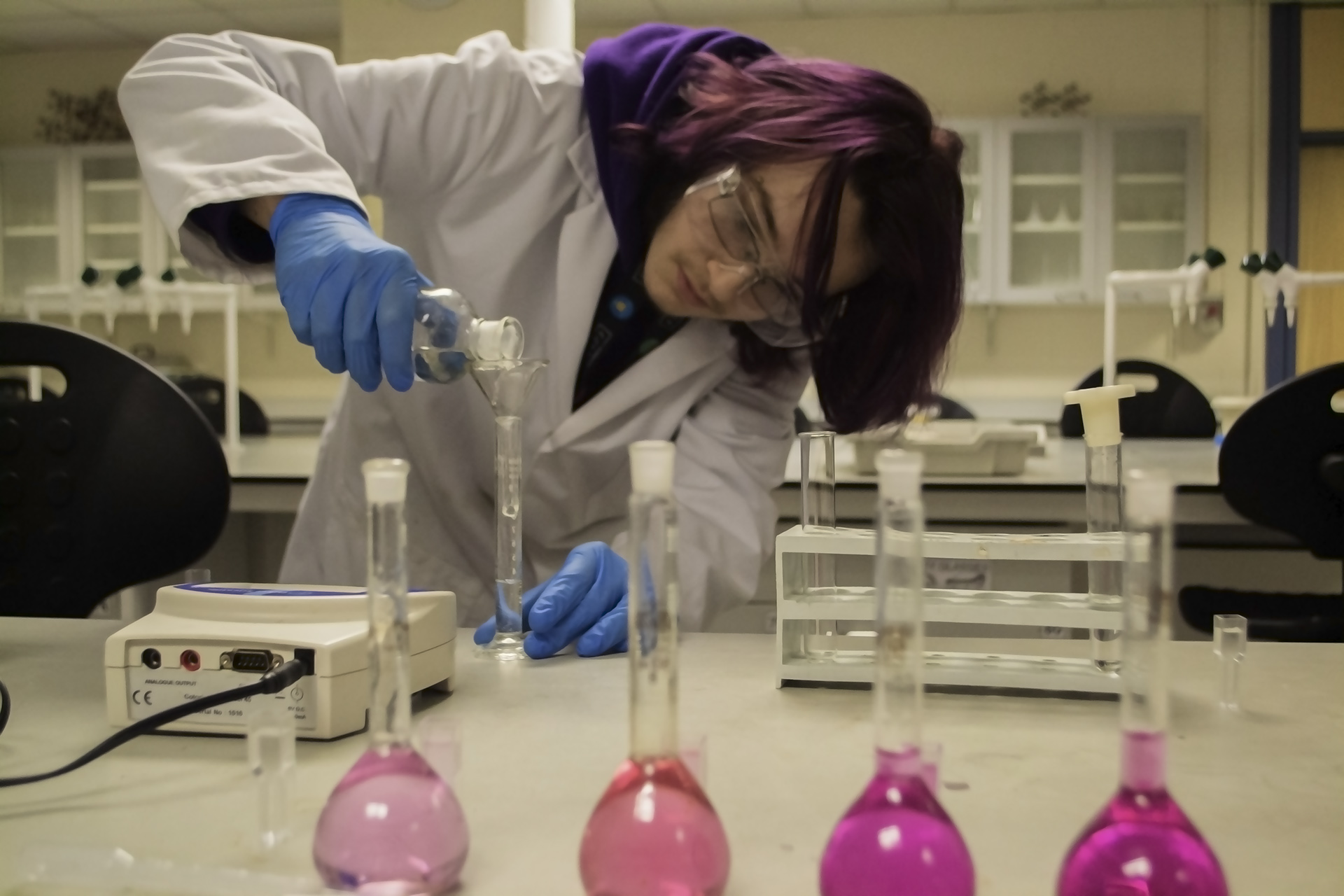 Science. Student in laboratory pouring liquid into measuring tube