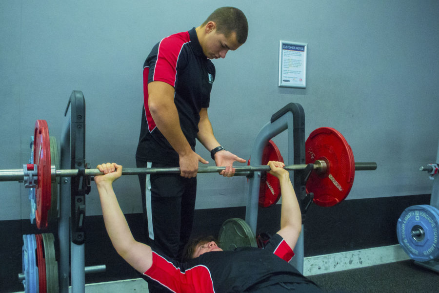 Sports Fitness. Student lifting weights with spotter