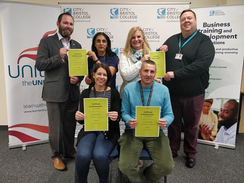 Students and tutors posing with certificates