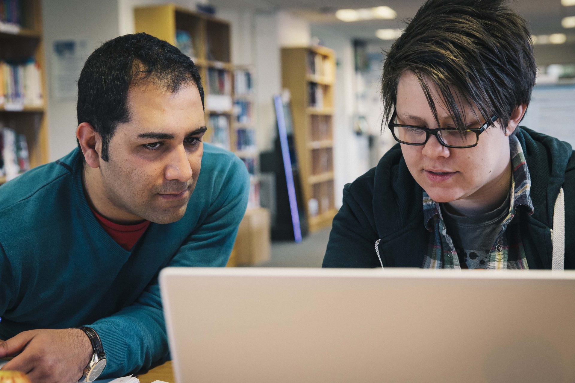 Hirad Babakhani and Anna Nicholls work on a laptop in Ashley Down Library