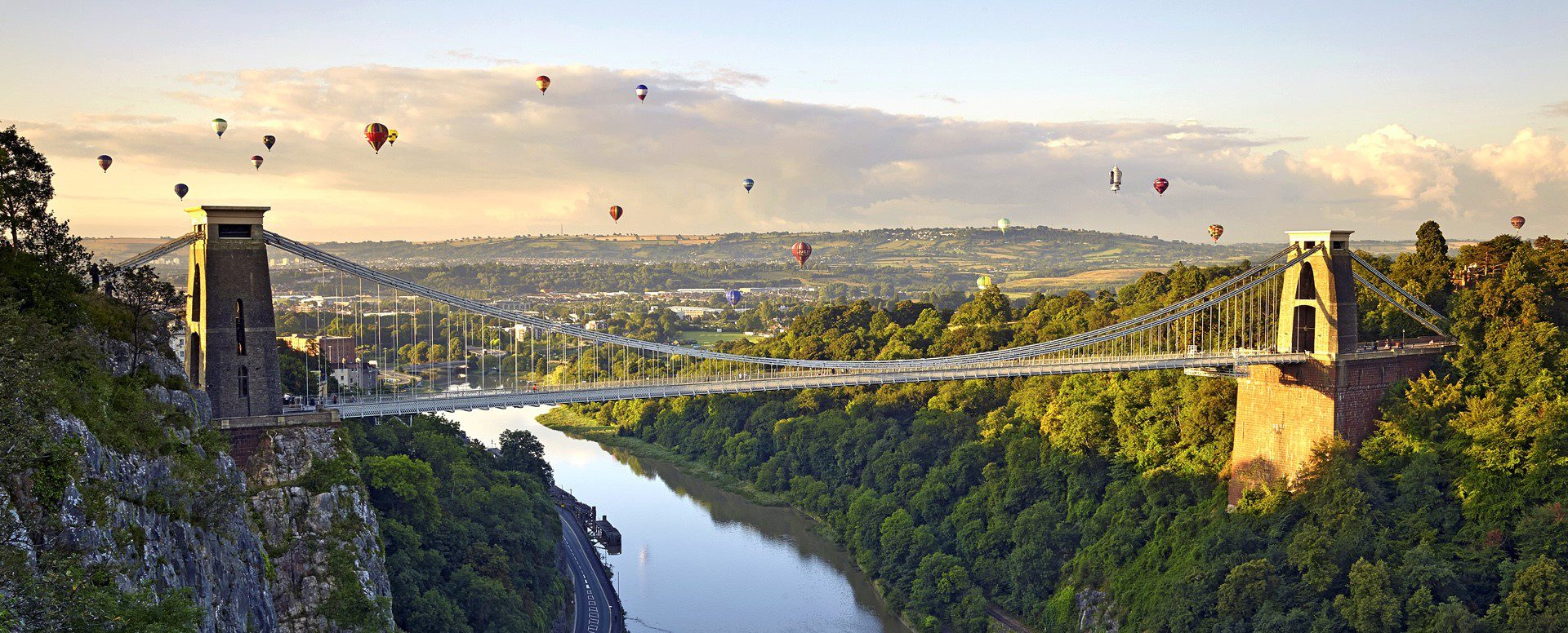 Picturesque shot of Clifton Suspension Bridge lit by the sun with around 15 hot air-balloons in the distance.