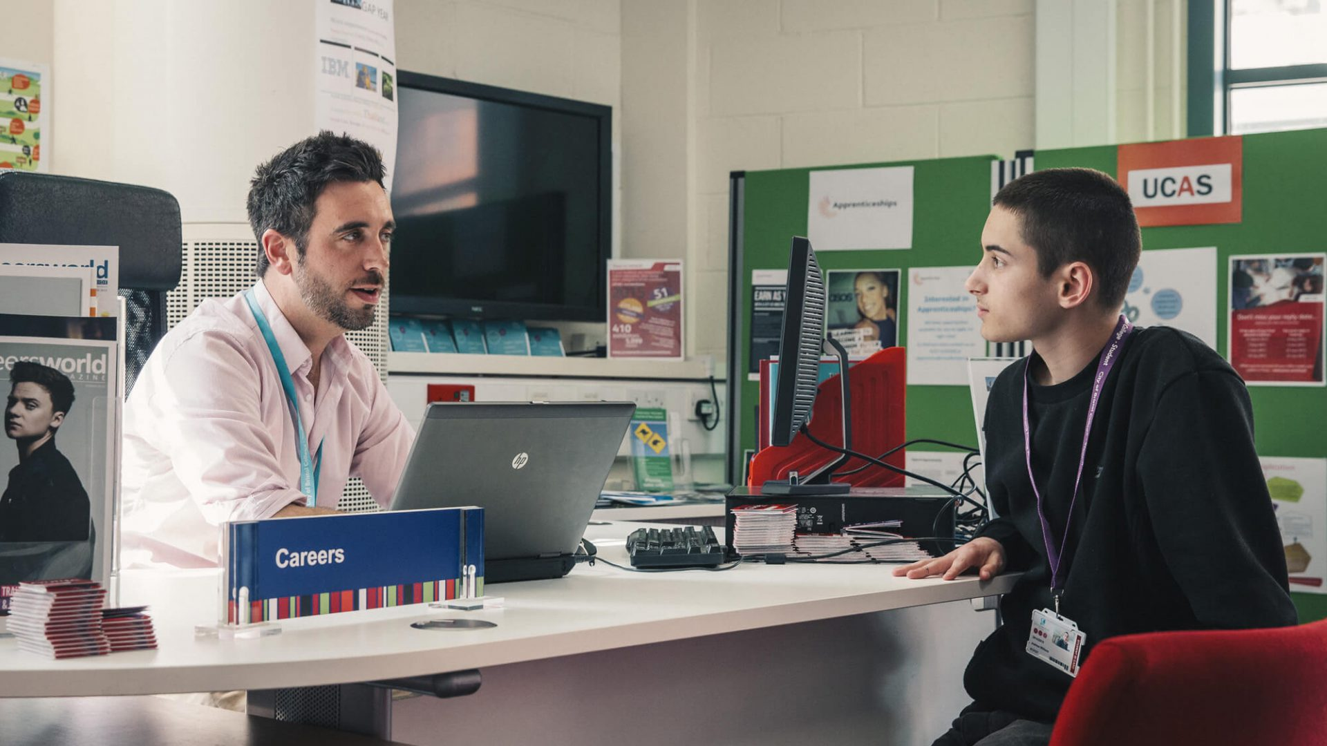 A member of staff speaks with a seated student in a classroom