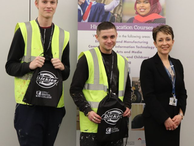 Two students pose with Emma Jarman, holding bags branded with 'Dickies'
