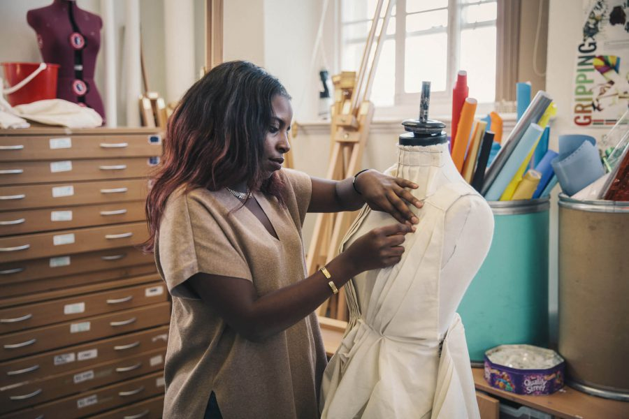 Fashion student works on a dress in an art-room in evening, part-time class