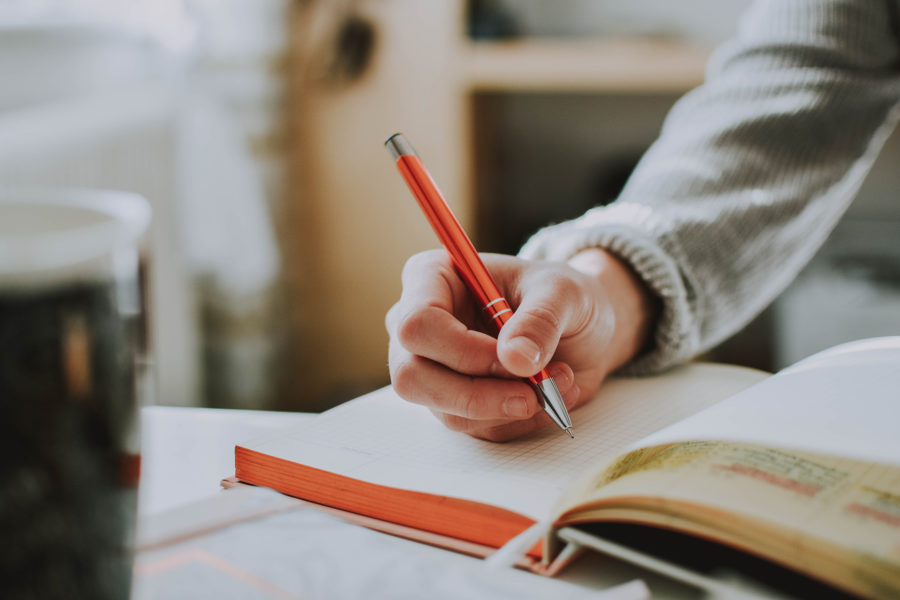 Person writing in book