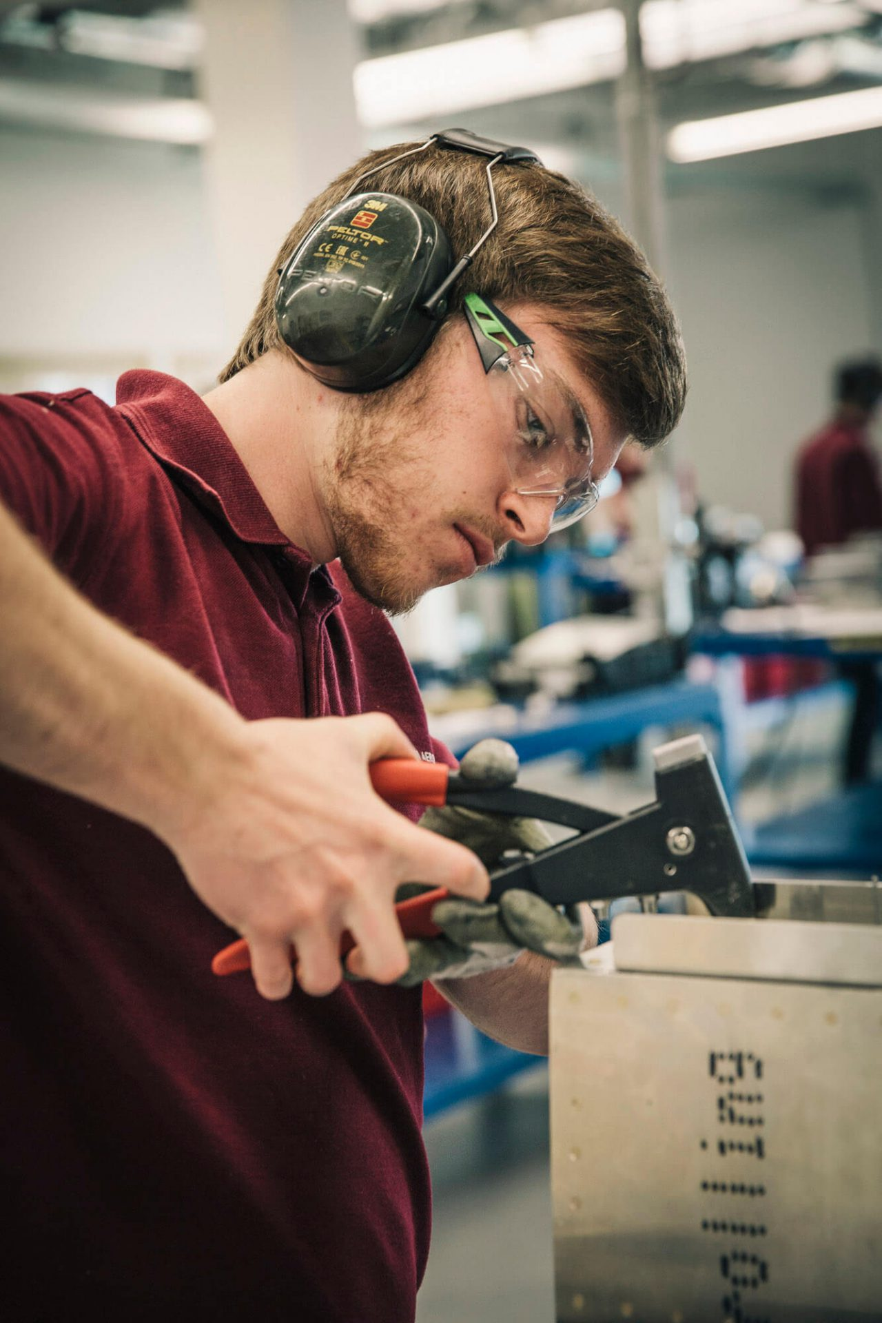 A GKN engineering student works with ear-defenders and goggles on