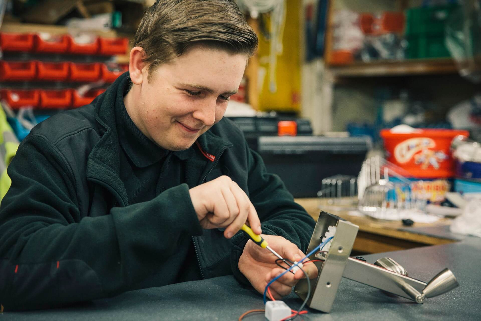 Hilton apprentice, Ross Budd works on some lights at a workbench