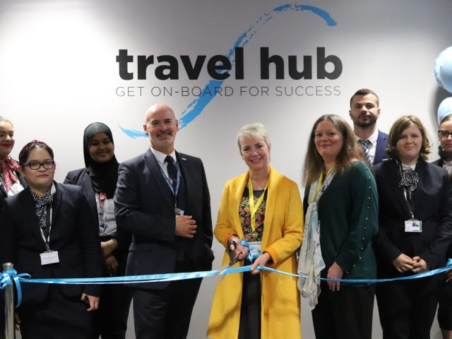 MP Karin Smyth cuts a ribbon for the travel hub. Students and staff are around her