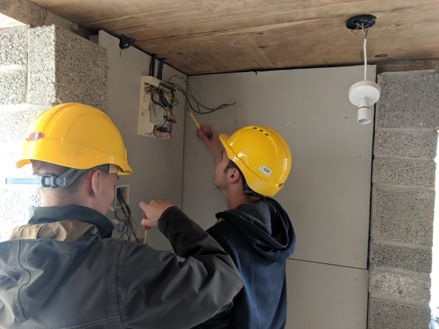 Electrical students in hard-hats work on a fuse box