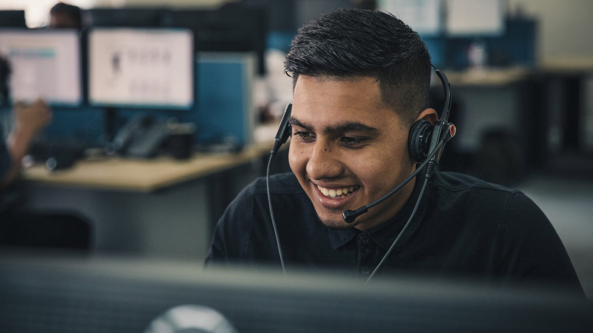 Young man smiles as he answers the phone in a call centre