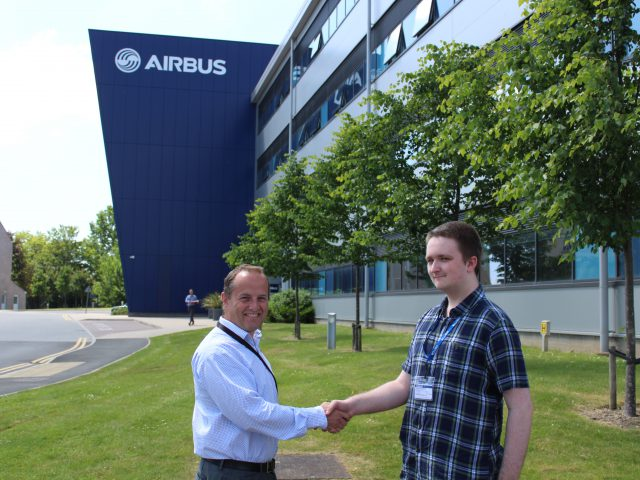Cameron Sidders, student, shakes hands with David Best, Head of Strategy & Business Development at Airbus