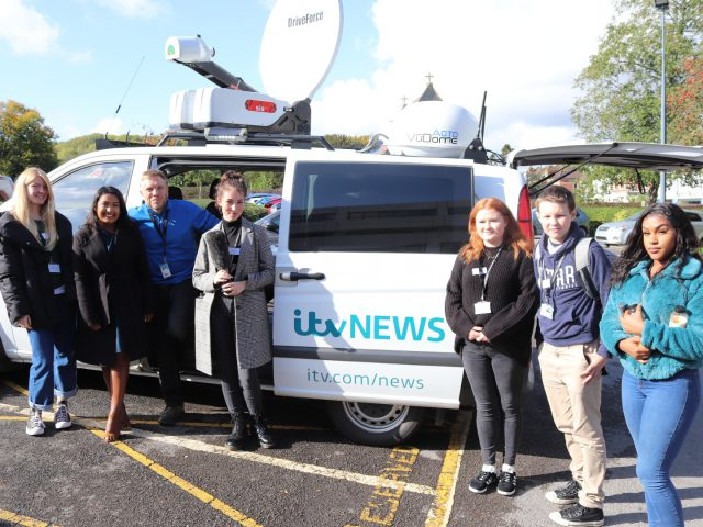 Students stand for a photo in-front of an ITV news van