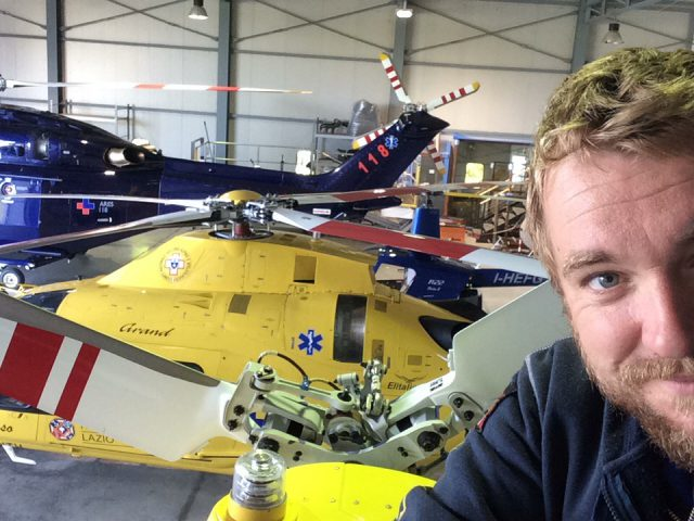 Jay Meakin takes a selfie with various helicopters in a warehouse