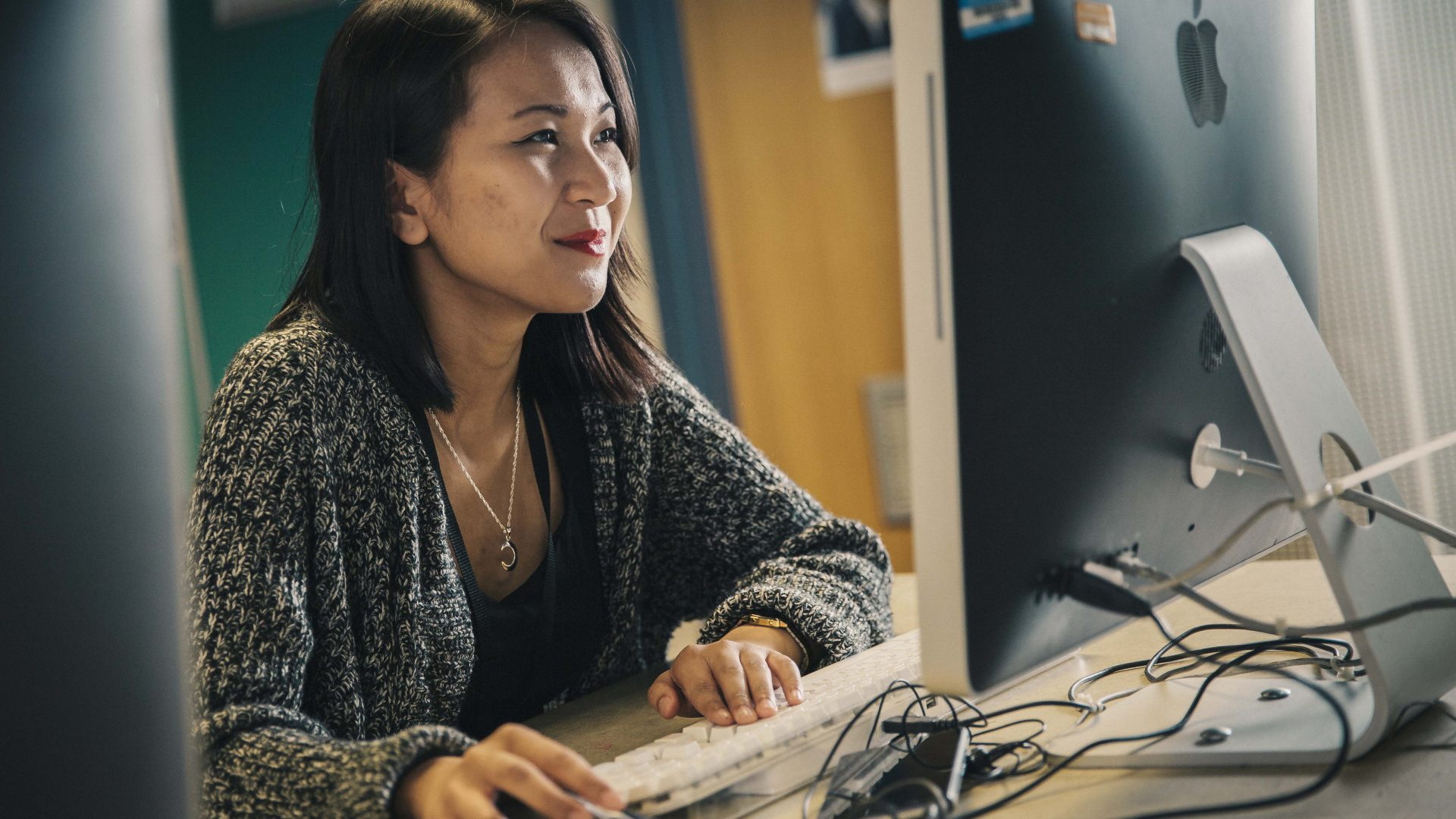Student, Patricia De Guzman uses a computer in the Mac Suite