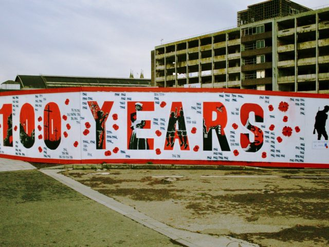 "Mural commemorating 100 years the Armistance Centenary. ""100 years"" is written in bold red, surrounded by poppies and notches to indicate the death toll."
