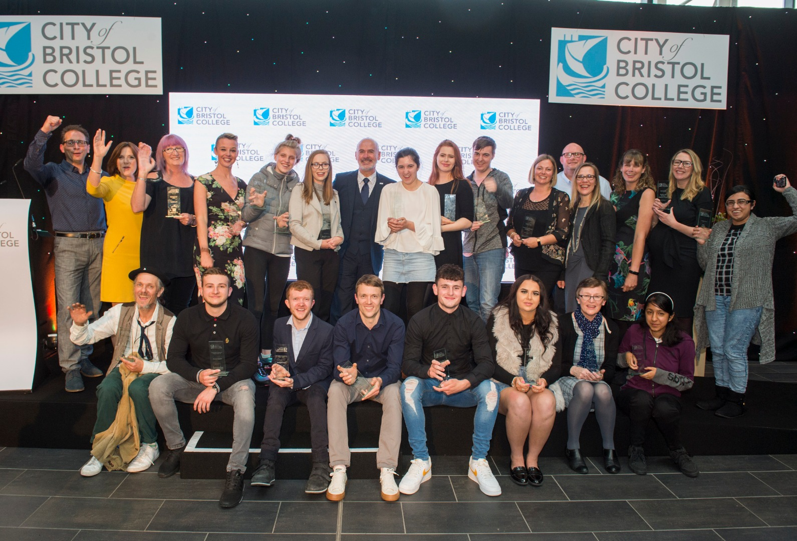 Students of City of Bristol College celebrate on stage as they hold their awards