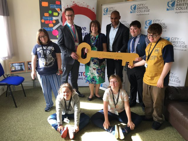 Young people at the Brislington Centre stand as staff hold an over-sized, cardboard key