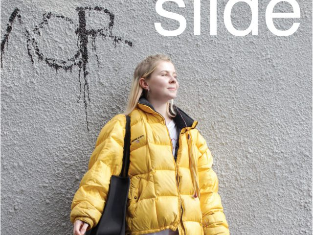 Poster for 'Slide'. A young woman is standing in-front of graffiti.