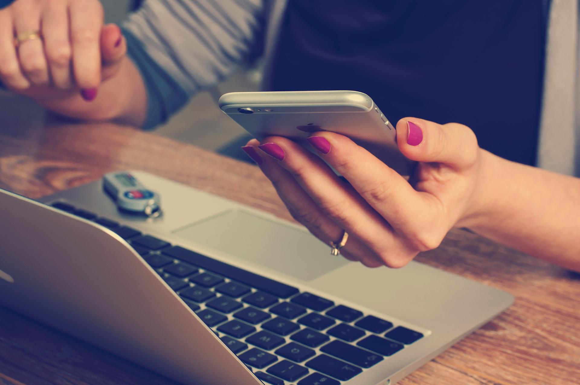 Student at computer, checking phone
