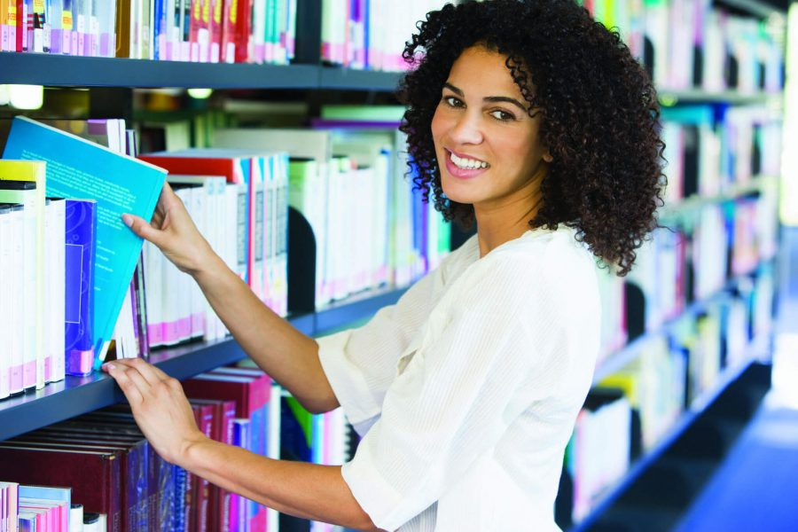 A woman pulls a book of a library shelf